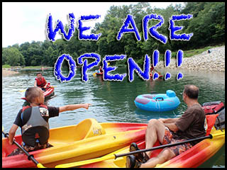 family floating in kayaks with announcement that the campground is open
